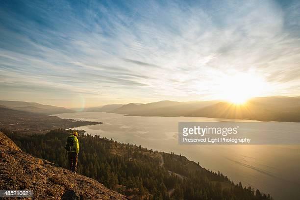 Male hiker watching sunset over Okanagan Lake, Naramata, British Columbia, Canada