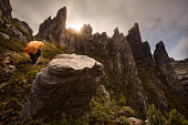 Male hiker with a backpack hiking amongst cliffs and pinnacles, Western Arthur range, South West National Park, Tasmania, Australia