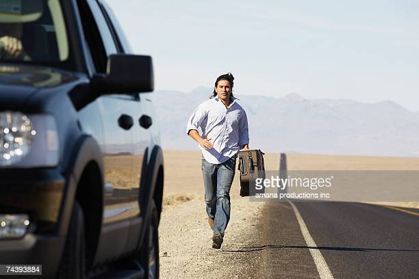 Male hitchhiker running towards car