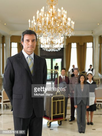 Male hotel manager standing in foyer, staff in background, portrait