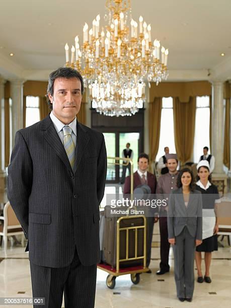 Macho hotel gerente em pé a entrada, no fundo, portr pessoal