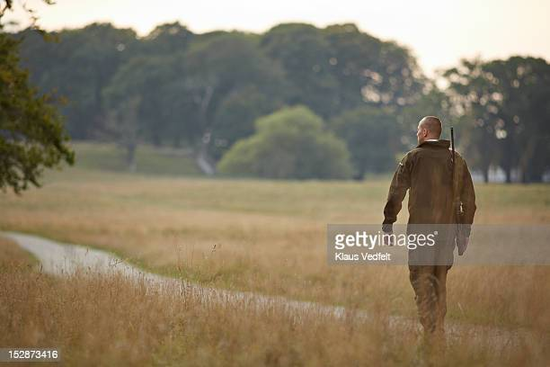 Male hunter walking on small gravel road