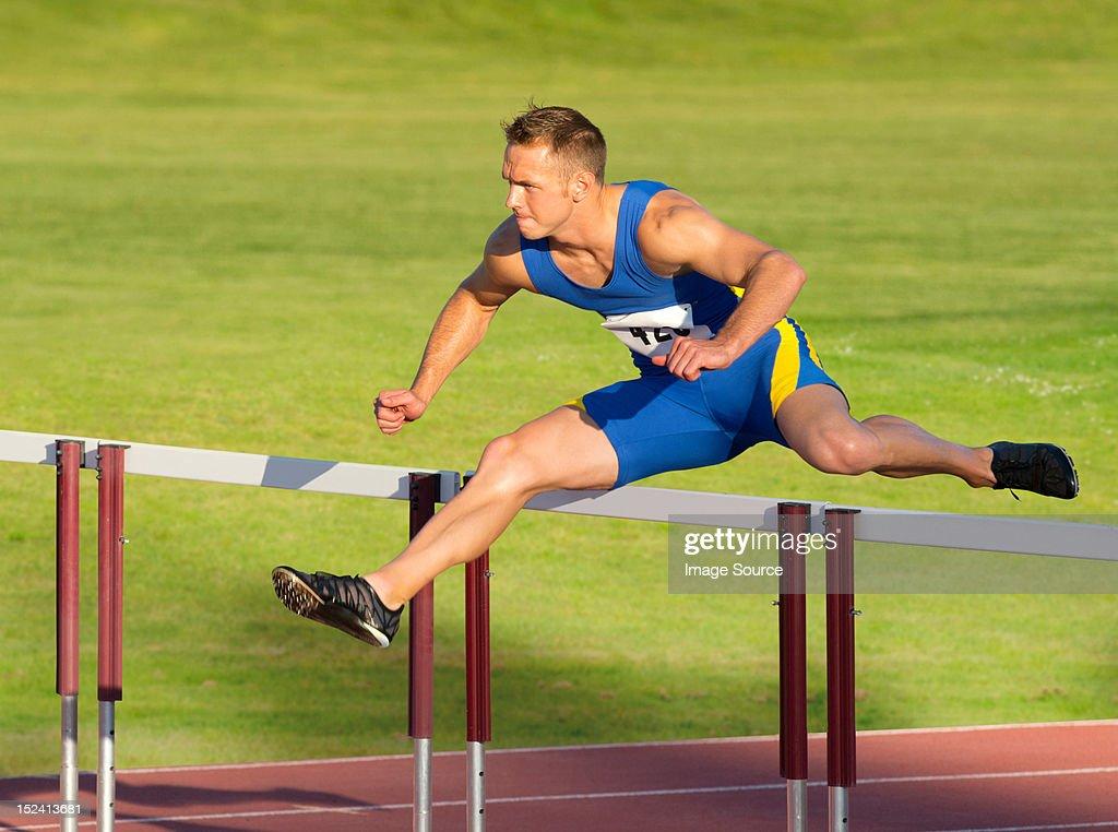 Male hurdler clearing hurdle : Stock Photo