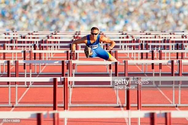 Male hurdler clearing hurdles