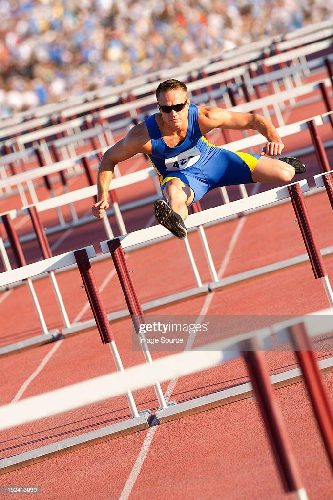 Male hurdler clearing hurdles : Stock Photo