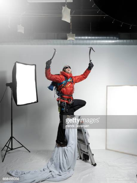 Male ice climber at the summit in a studio