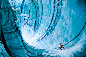 Male ice climber exploring ice cave, low angle view