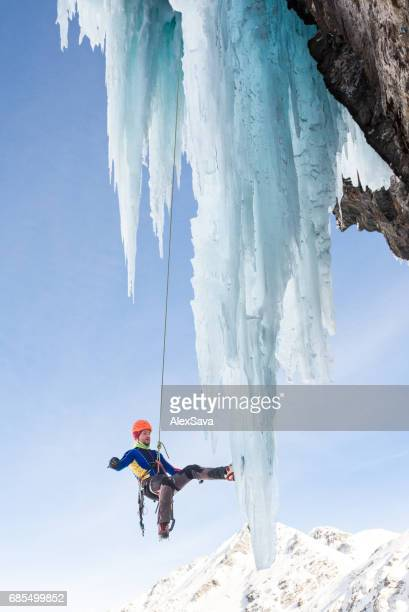 Male ice climber hanging on massive icicle