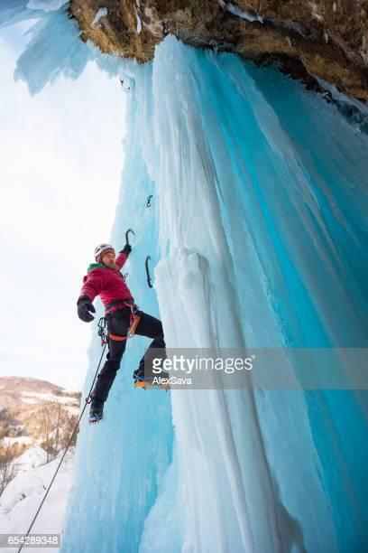 Male ice climber holding on a single ice axe