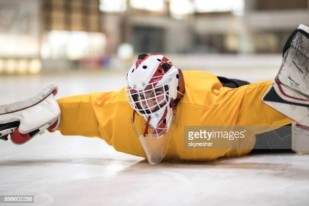 Gardien de but de hockey sur glace masculin s'amuser tout en se trouvant sur la glace dans une patinoire.