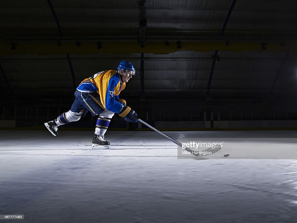 Male Ice Hockey player skating with stick