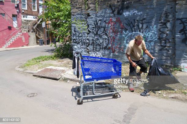 A male identified only as Bruce cleans up an area near the make shift heroin camp under the Emerald Street Bridge in the Kensington Section of...