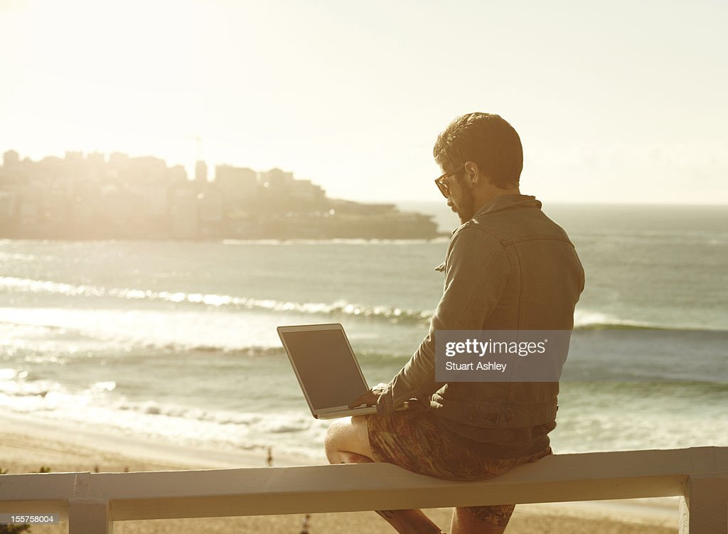 Male in Bondi with laptop : Stock Photo