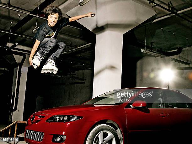 Male inline skater jumping over car
