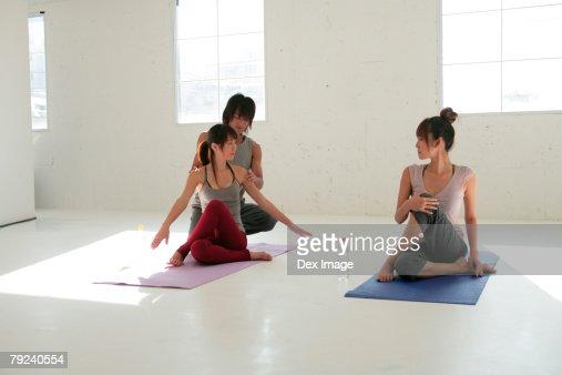 Male instructor coaching two women in yoga class : Stock Photo