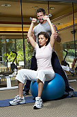 Male instructor helping woman in gym