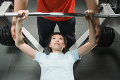 Male instructor training woman with bar bells in gym, high angle view