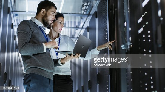 Male IT Specialist Holds Laptop and Discusses Work with Female Server Technician. They're Standing in Data Center, Rack Server Cabinet is Open. : Stock Photo