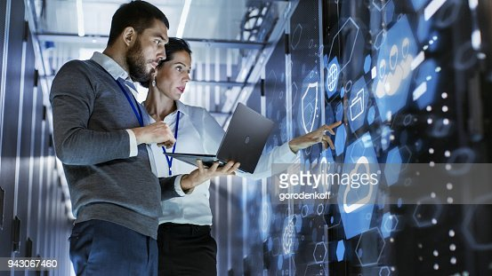 Male IT Specialist Holds Laptop and Discusses Work with Female Server Technician. They're Standing in Data Center, Rack Server Cabinet with Cloud Server Icon and Visualization. : Stock Photo