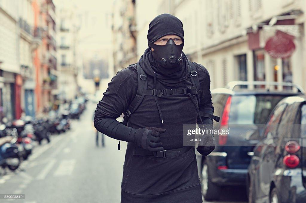 Male jogging in black in Paris street wearing breathing apparatus : Stock Photo