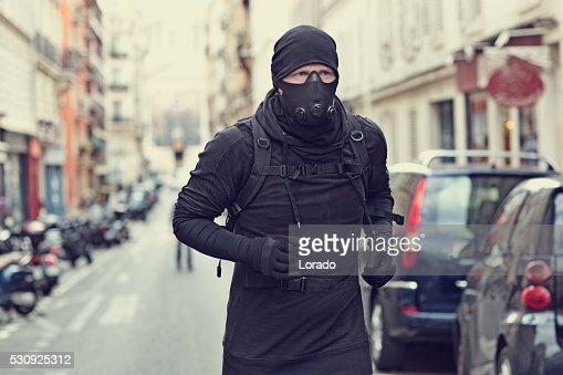 Male jogging in black in Paris street wearing breathing apparatus