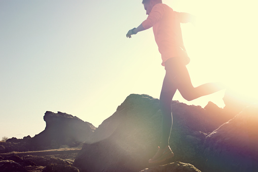Male jumping and leaping over rocks in amazing sun