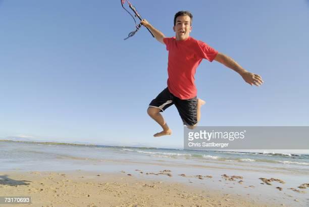 Male kite surfer jumping on beach