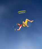Male kiteboarder in midair, holding board in hand, low angle view