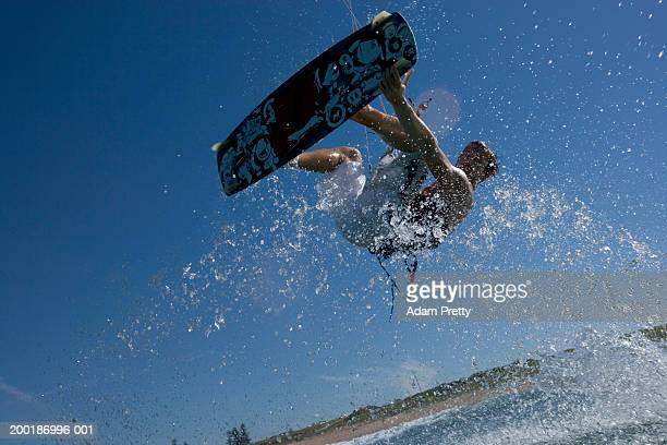 Male kiteboarder mid-air, one hand gripping board, low angle view