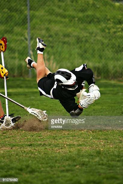 Male Lacrosse Player Flies in Horizontal Dive Capturing Ball