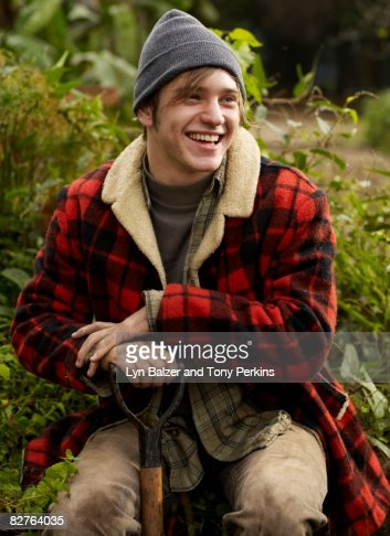 Male leaning on shovel in the garden : Stock Photo