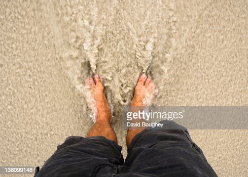 Male legs in surf on beach : Foto de stock