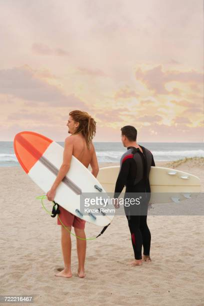Male lifeguard and surfer looking out to sea from beach