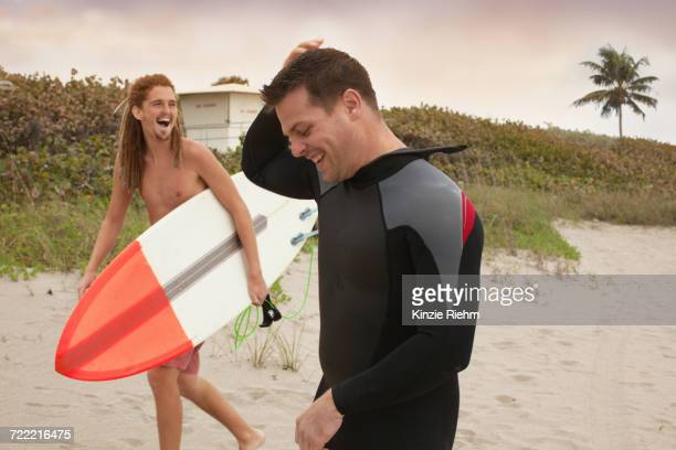 Male lifeguard chatting to surfer on beach