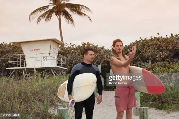 Male lifeguard having discussion with surfer on beach
