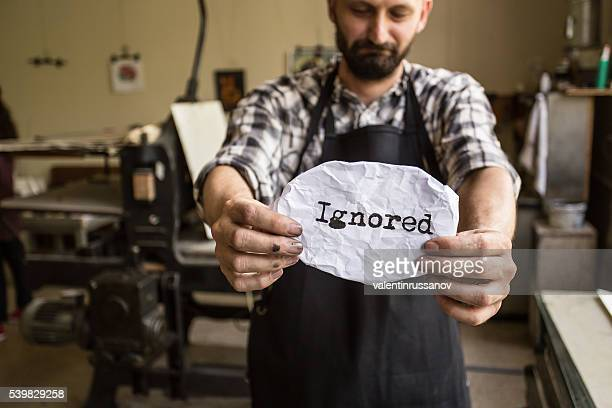 Male lithography worker holding a message 'ignored'