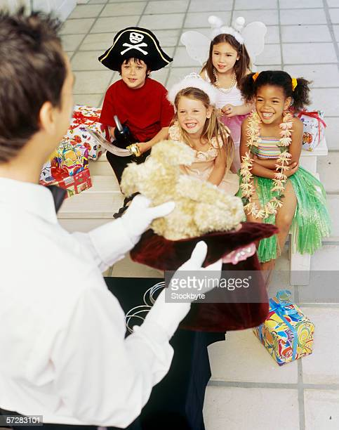 Male magician performing in front of a group of children at a birthday party