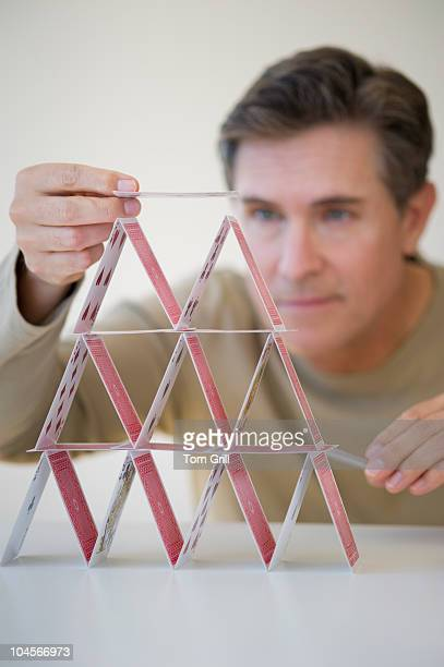 Male making house of cards