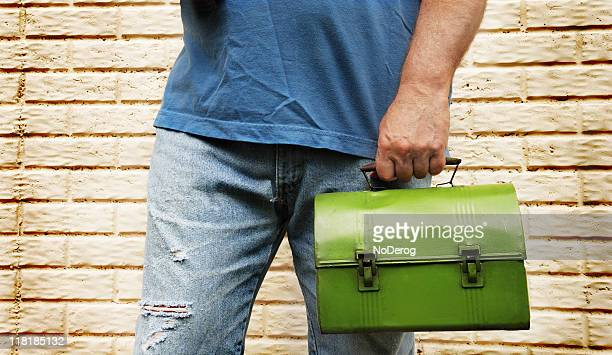 Male manual laborer worker in ripped jeans with lunch box