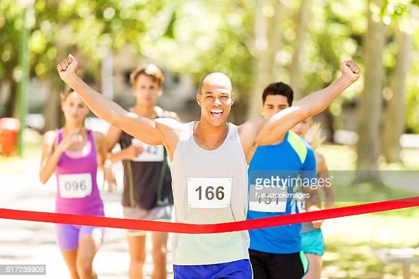 Hombre de corredor de maratón de cruzar alcanzar la línea de meta