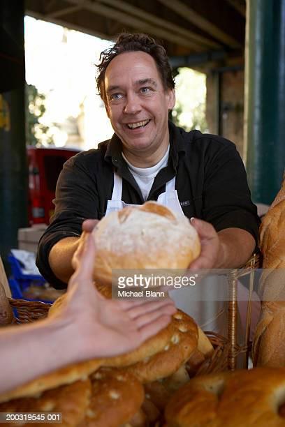 Male market stallholder handing loaf to customer, smiling