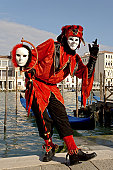 Male mask with red harlequin costume at carnival in Venice