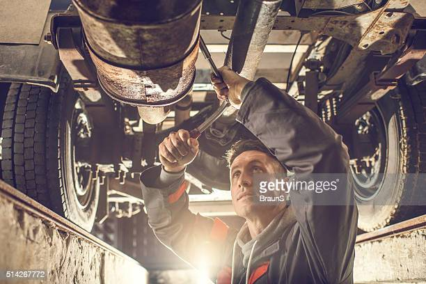 Male mechanic using socket wrench while working on chassis.