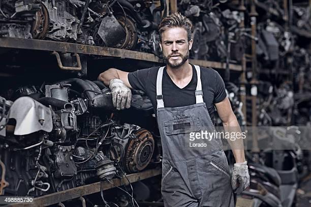 male mechanic working at junkyard engine storage