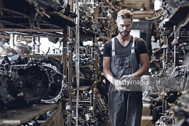 male mechanic working at junkyard engine storage