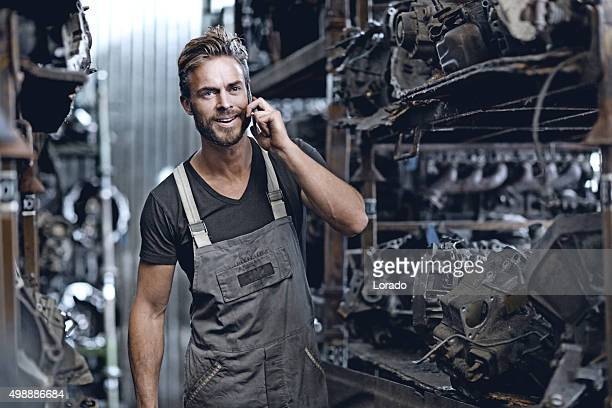 Mâle mécanicien travaillant sur junkyard de rangement