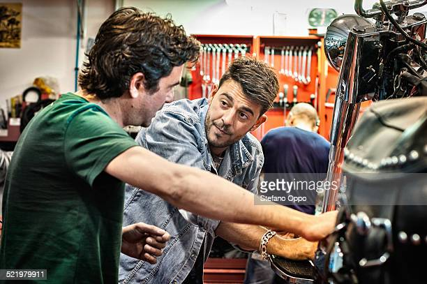 Male mechanics chatting in motorcycle workshop