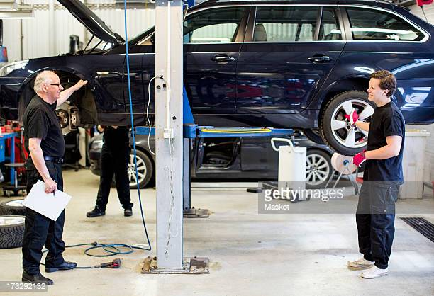 Male mechanics discussing while standing against car lifted on jack at workshop