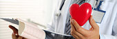 Male medicine doctor hands hold red toy heart and cardiogram chart on clipboard pad. Cardio therapeutist, physician make cardiac physical, pulse rate measure, arrhythmia concept. Letterbox view
