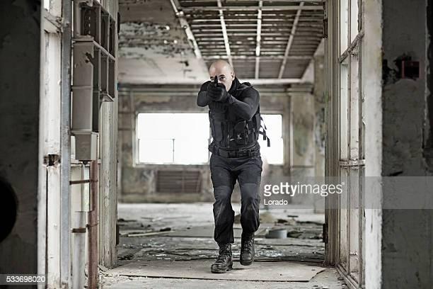 Male military swat team member holding gun in abandoned warehouse